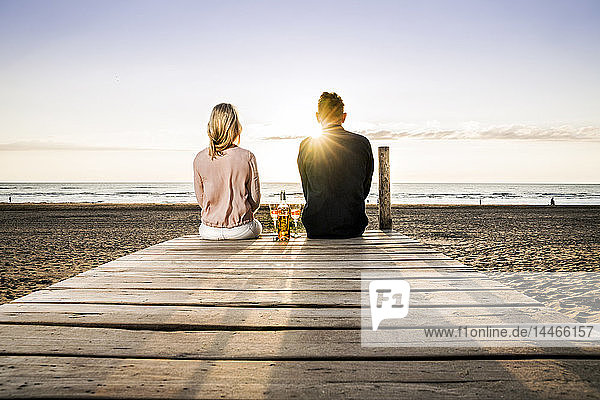 Couple with wine glasses sitting on boardwalk on the beach at sunset