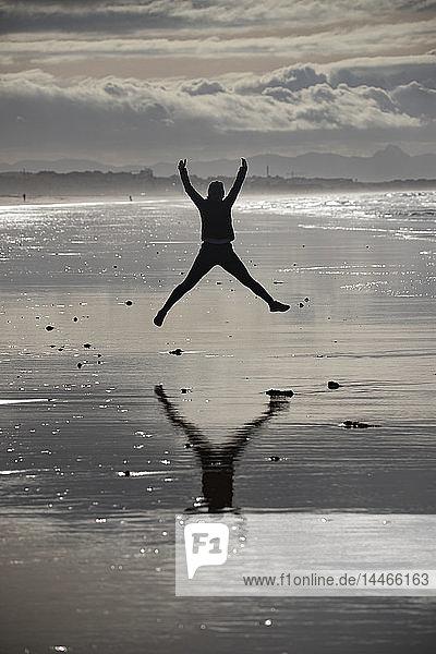Joggerin springt am Strand