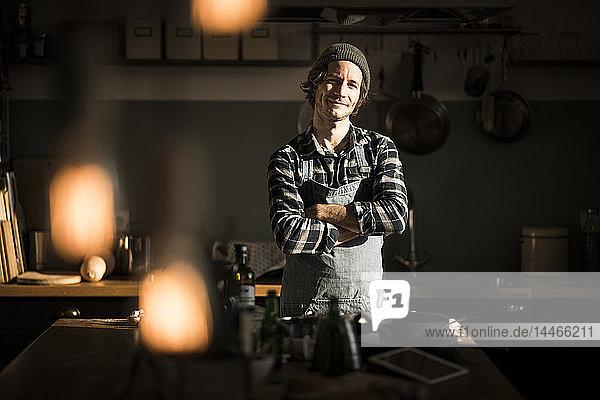 Stolzer Hobbykoch  der mit verschränkten Armen in seiner Küche steht