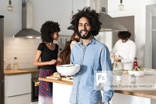 Freunde bereiten in der Küche ein Abendessen vor  Mann serviert Salat