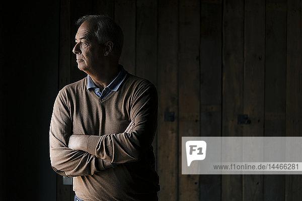Schwerer leitender Geschäftsmann vor Holzwand mit seitlichem Blick
