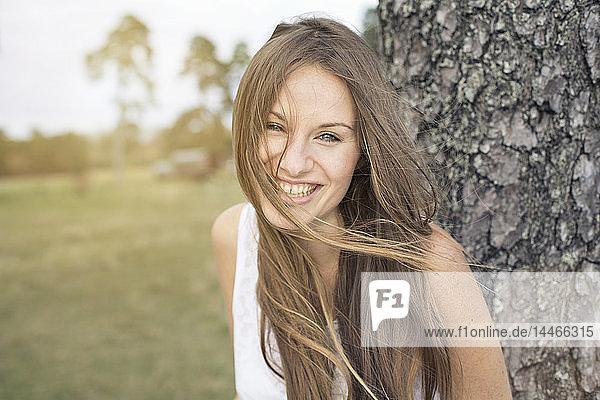 Porträt einer lachenden jungen Frau  die sich an einen Baumstamm lehnt