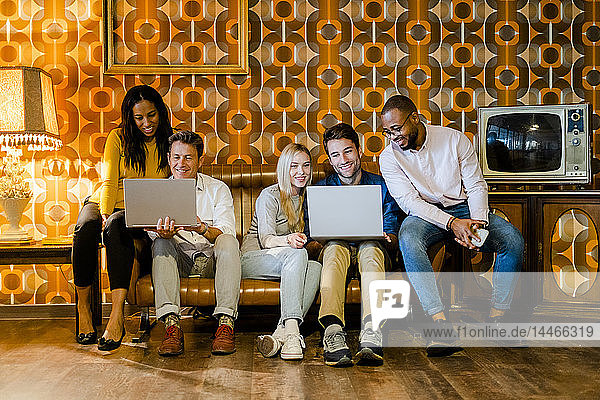 Group of smiling people sitting on couch in vintage living room sharing laptops
