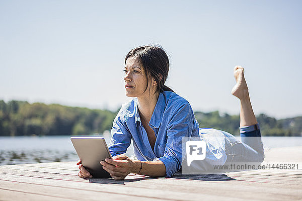 Mature woman working at a lake  using digita tablet on a jetty