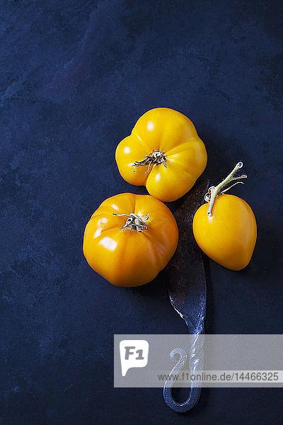 Drei Tomaten 'Golden Jubilee' und ein Messer auf dunklem Hintergrund