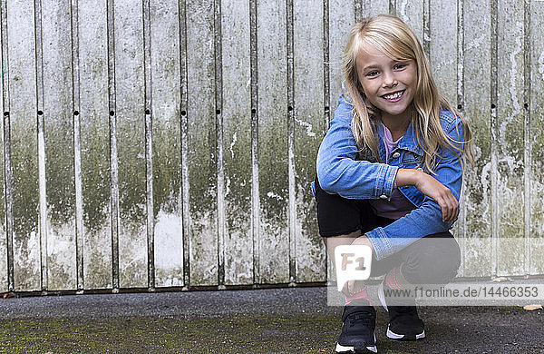 Portrait of smiling blond girl crouching in front of wooden wall