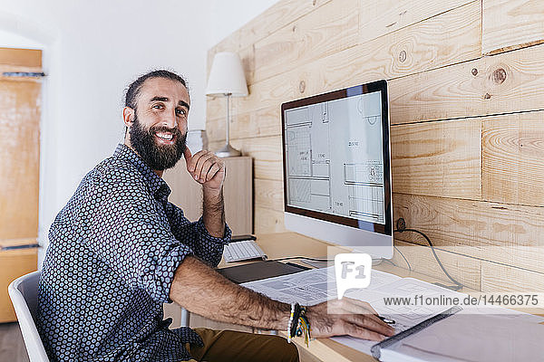 Portrait of happy young architect working at home with blueprints and computer