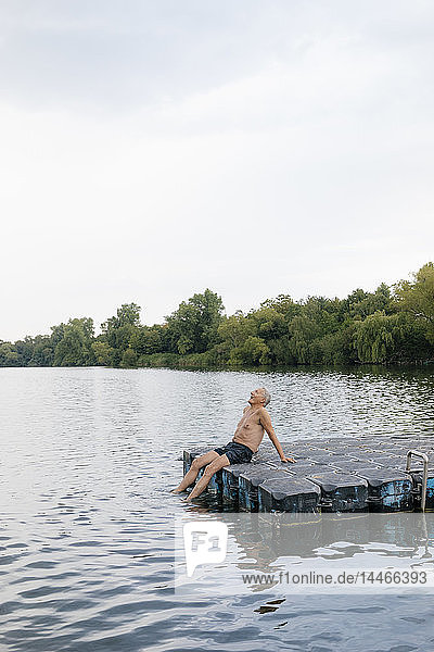 Senior man sitting on raft in a lake