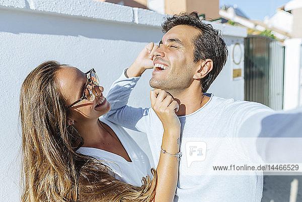 Glückliches  verspieltes Paar an einem sonnigen Tag im Freien