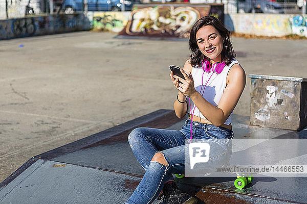 Porträt einer lächelnden jungen Frau mit Kopfhörer und Handy in einem Skatepark