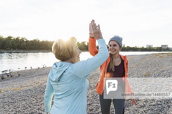 Großmutter und Enkelin High-Five nach der Ausbildung am Fluss
