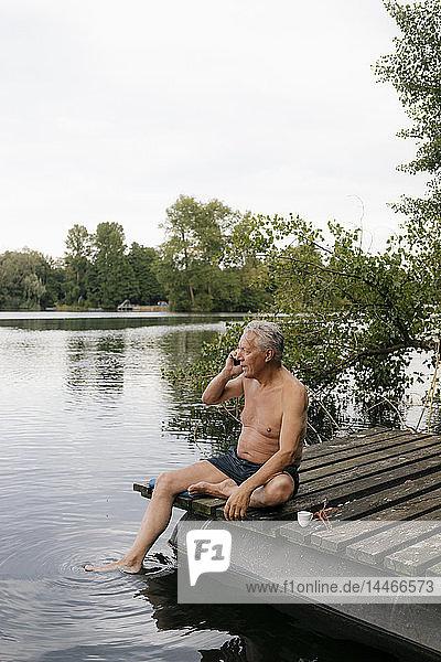 Älterer Mann sitzt auf einem Steg an einem See und telefoniert