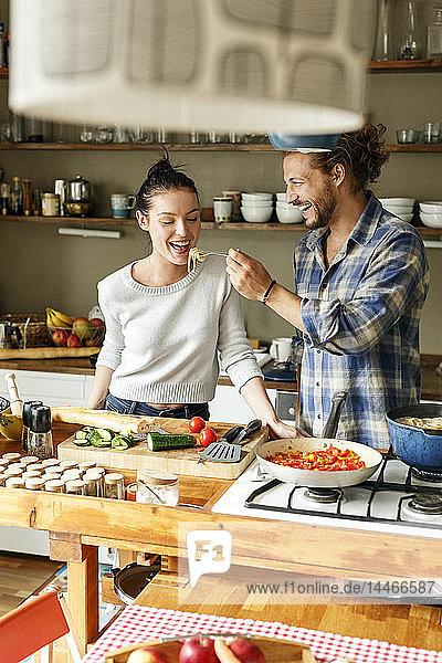 Junges Paar bereitet gemeinsam Essen zu  probiert Spaghetti