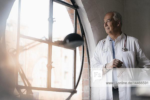 Leitender Arzt schaut in der medizinischen Praxis aus dem Fenster