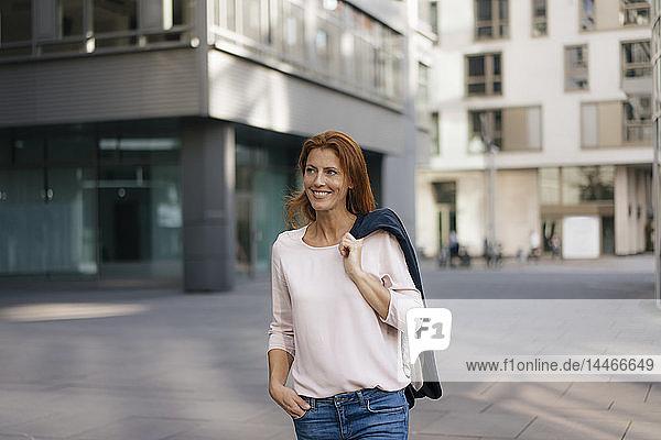 Lächelnde Geschäftsfrau im Freien in der Stadt