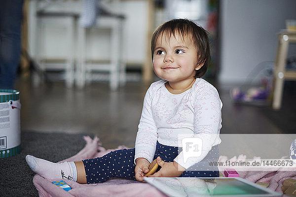 Süßes kleines Mädchen  das zu Hause auf dem Boden sitzt