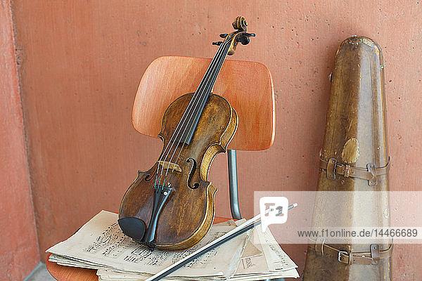 Geige  Bogen und Noten auf Holzstuhl mit Geigenkasten im Hintergrund