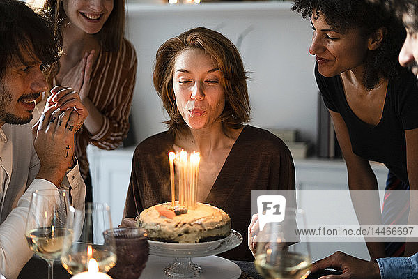 Friends celbrating birthday of a young woman  blowing out birthday candles