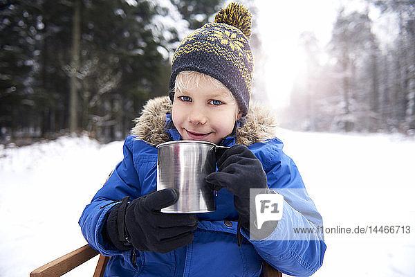 Portrait of smiling little boy sitting on sledge in winter forest drinking tea