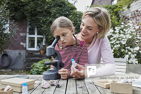 Mother and daughter using microscope together at garden table