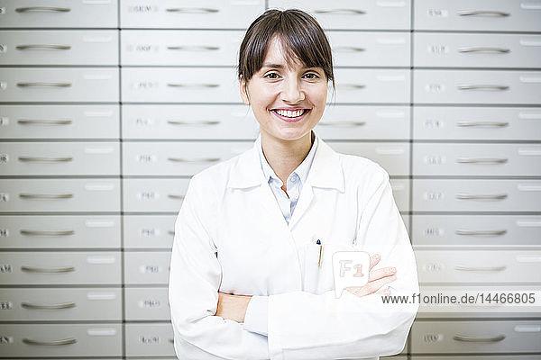 Porträt eines lächelnden Apothekers am Kabinett in der Apotheke