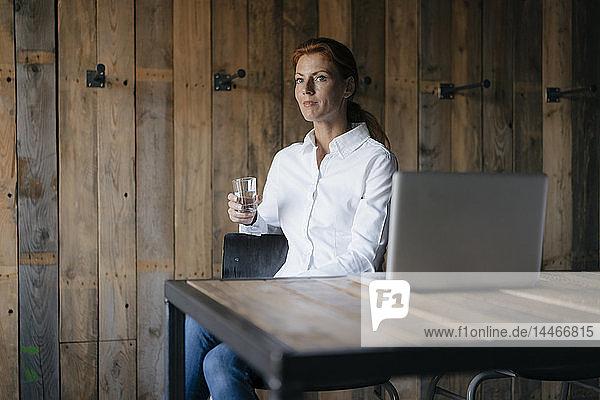 Geschäftsfrau sitzt am Schreibtisch mit einem Glas Wasser und einem Laptop