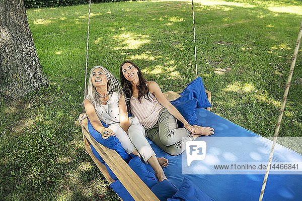Two women relaxing on a hanging bed in garden looking up
