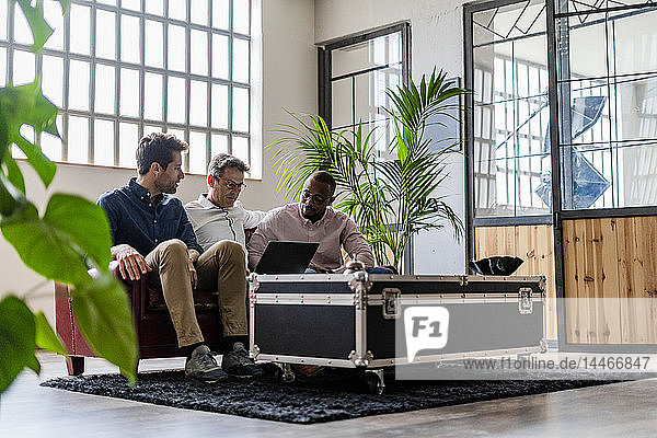 Three businessmen using laptop sitting on sofa in loft office