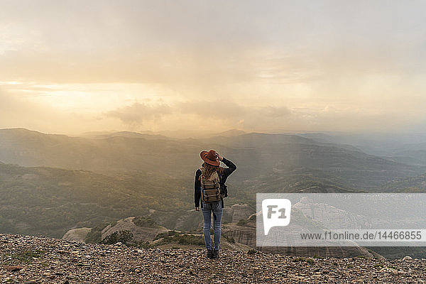 Frau mit Rückenlehne  auf Berg stehend  schaut auf Aussicht
