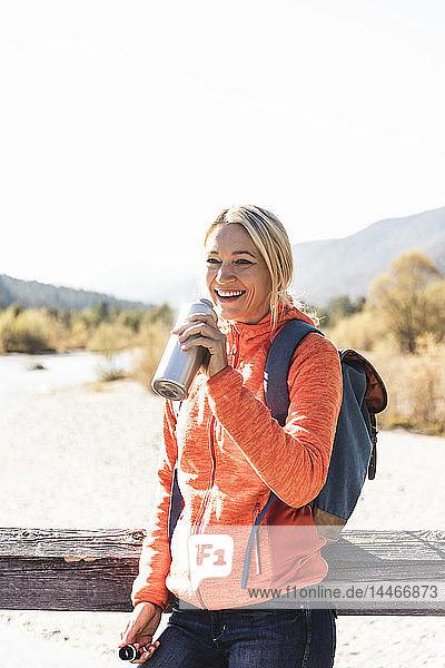 Österreich,  Alpen,  glückliche Frau auf einer Wanderung,  die aus der Flasche trinkt