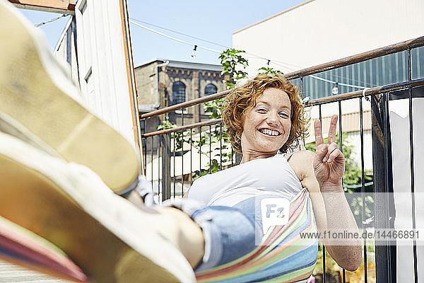 Glückliche junge Frau in Hängematte macht Siegeszeichen in städtischer Umgebung