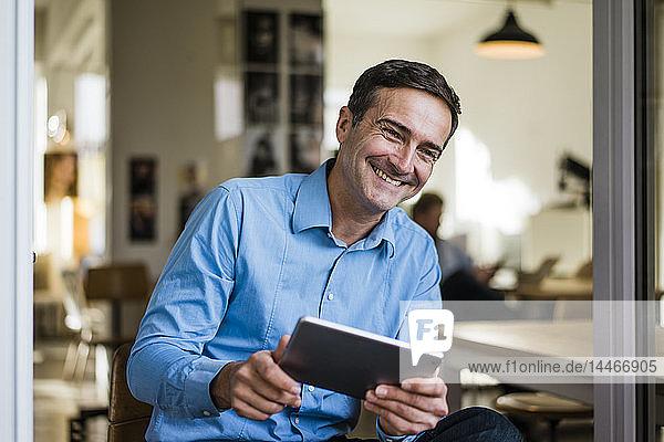 Lächelnder Geschäftsmann mit Tablette sitzt an offener französischer Tür