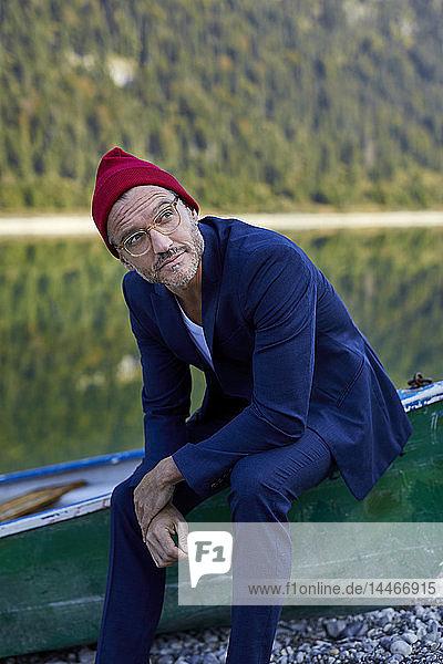 Porträt eines bärtigen  reifen Mannes mit roter Mütze und blauem Anzug am Seeufer