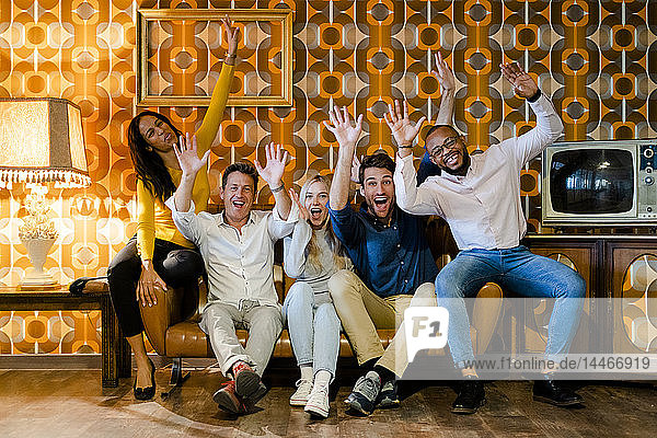 Group of happy people sitting on couch in vintage living room