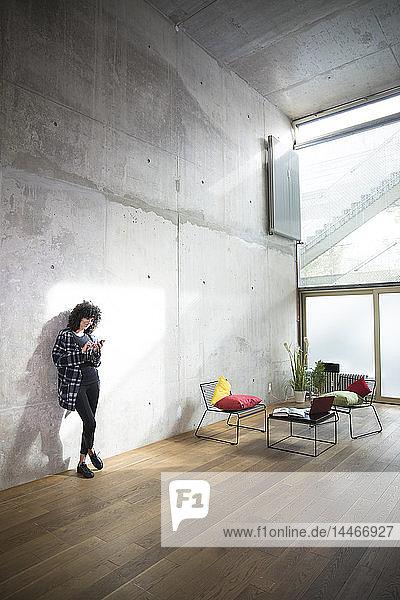 Frau lehnt mit Handy an Betonwand in einem Loft