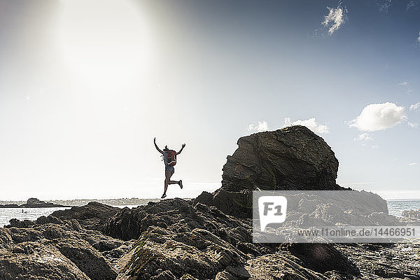 Young woman runnning and jumping on a rocky beach