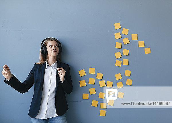 Junge Geschäftsfrau mit Kopfhörern  die Musik aufzählt