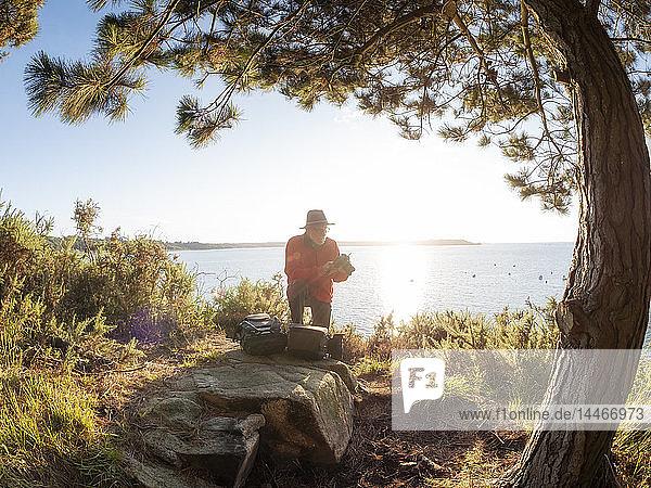 France,  Bretagne,  Bay near Perros-Guirec,  senior hiker with camera on viewpoint