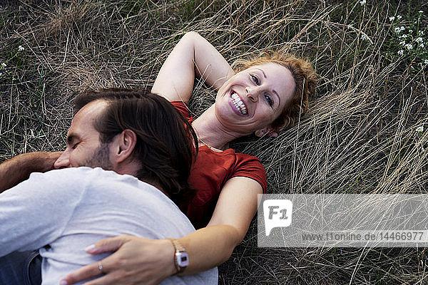 Glückliches Paar kuschelnd  auf einer Wiese liegend