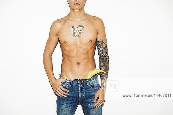 Halb bekleideter junger Mann mit einer Banane in der Jeans