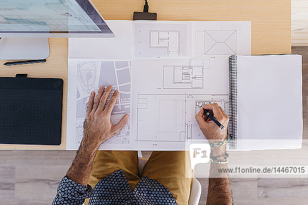Close-up of architect working at home on floor plan