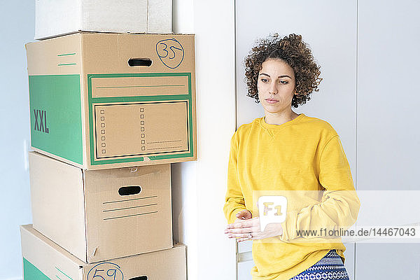 Seriöse Frau zu Hause mit Pappkartons