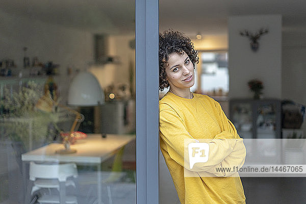 Porträt einer Frau  die sich zu Hause an die Terrassentür lehnt