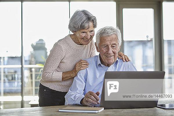 Portrait eines lächelnden älteren Paares mit Laptop