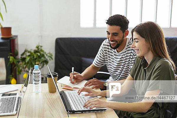 Lächelnde Kollegen arbeiten gemeinsam am Schreibtisch im Büro und teilen sich den Laptop