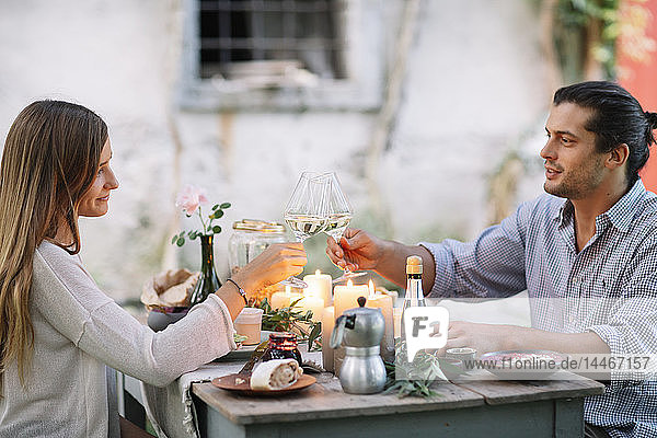 Couple having a romantic candlelight meal clinking wine glasses