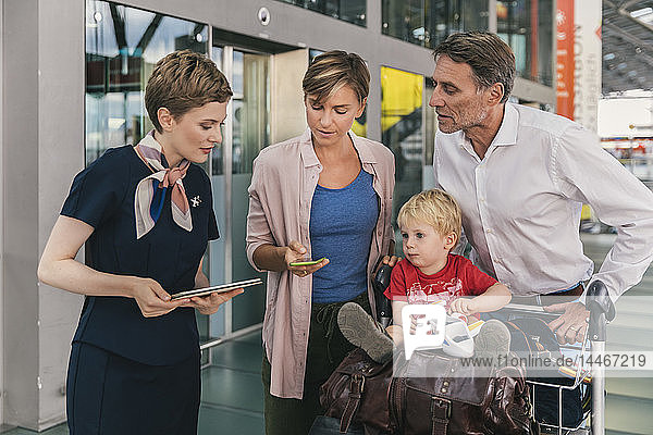 Airline employee assisting family with baggage cart at the airport