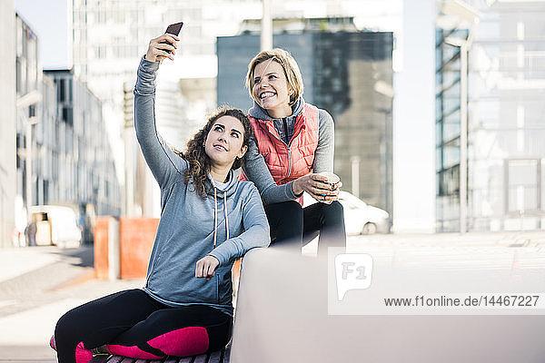 Girlfriends taking a break after training  using smartphone