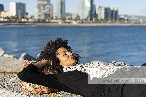 Spanien  Barcelona  schwarz gekleidete Frau entspannt sich bei Sonnenlicht an einer Wand