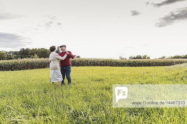 Älteres Paar tanzt in ländlicher Landschaft